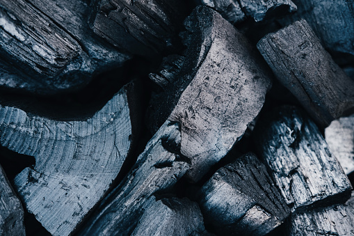 Black coals close up background. Burnt wood texture. Beams in grill, ashes in barbeque top view. Natural smouldering charcoal heap abstract backdrop. Grey firewood minimalistic composition