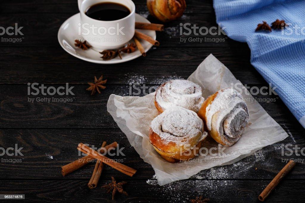 Black coffee and cinnamon rolls with powdered sugar - Zbiór zdjęć royalty-free (Brązowy)