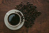 istock Black coffee and coffee beans on wooden table. 1332286548