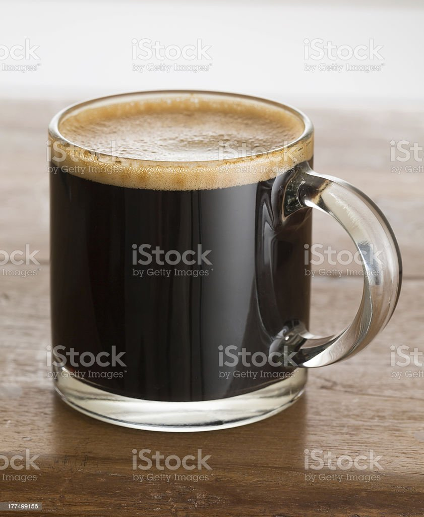 Black coffee and froth in glass mug wood table stock photo