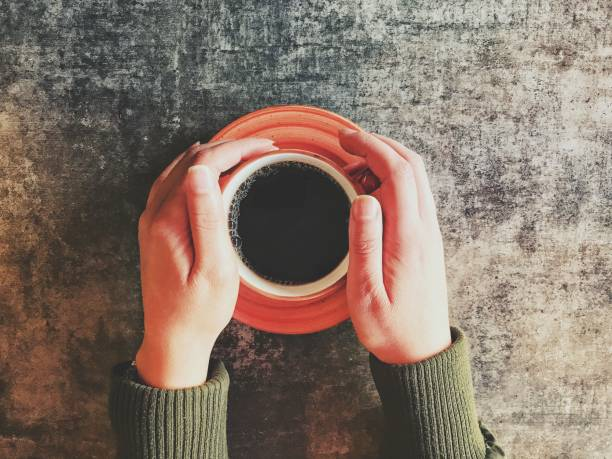 black coffee and hands a cup of black coffee in hands black coffee stock pictures, royalty-free photos & images