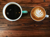 black coffee and latte coffee on the vintage wooden table. Black and white coffee.