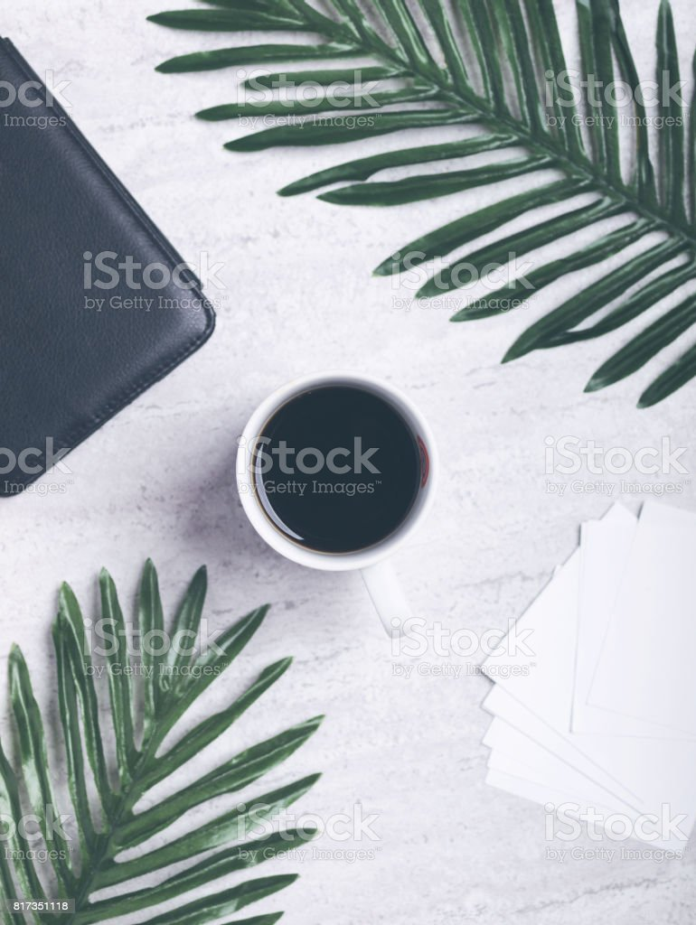 Black coffee and office supplies like white paper and big green tropical leaves on grey concrete background. Flat lay. Top view. Copy space. stock photo