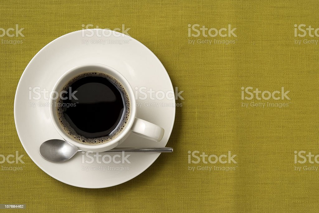 Black coffee and spoon on green tablecloth with copy space royalty-free stock photo