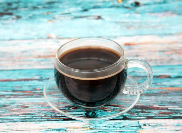 Schwarzer Kaffee in einer Glastasse auf blauem Holzhintergrund – Foto