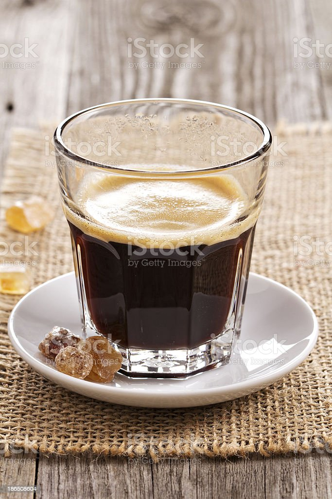 Black coffee in a glass with brown sugar crystals royalty-free stock photo