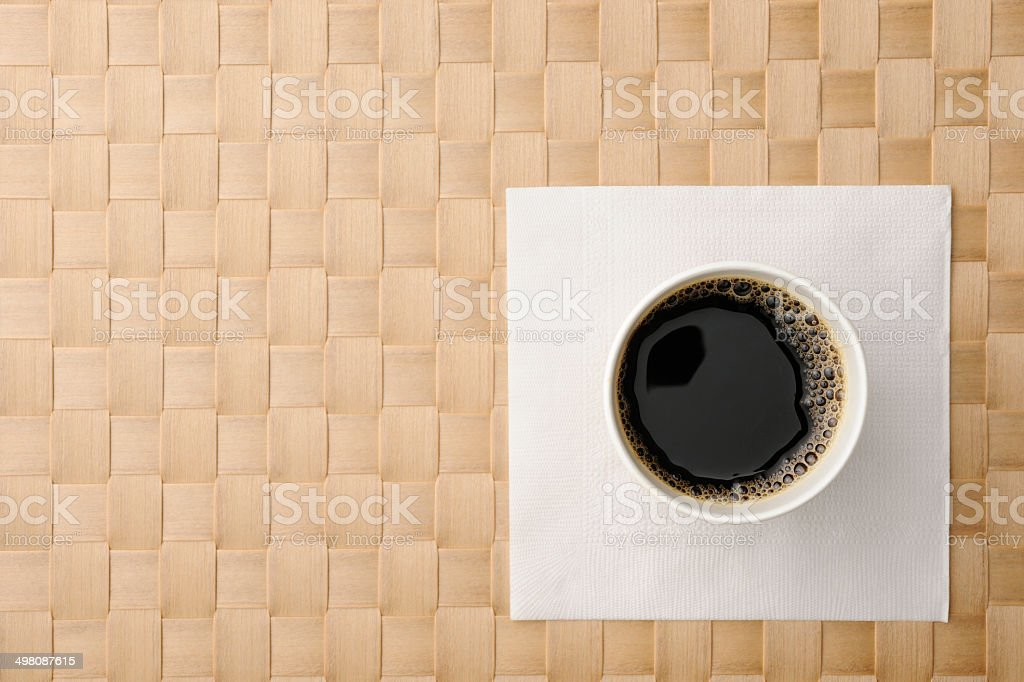 Black coffee in disposable cup with napkin on place mat royalty-free stock photo