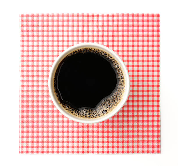 Black coffee in disposable cup with napkin on white background Overhead shot of black coffee in white disposable cup with mesh napkin, isolated on white background with clipping path. disposable cup stock pictures, royalty-free photos & images