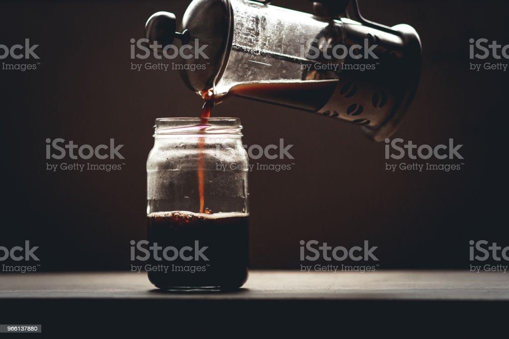 Svart kaffe i glas i svagt ljus fönster ljus - Royaltyfri Bord Bildbanksbilder