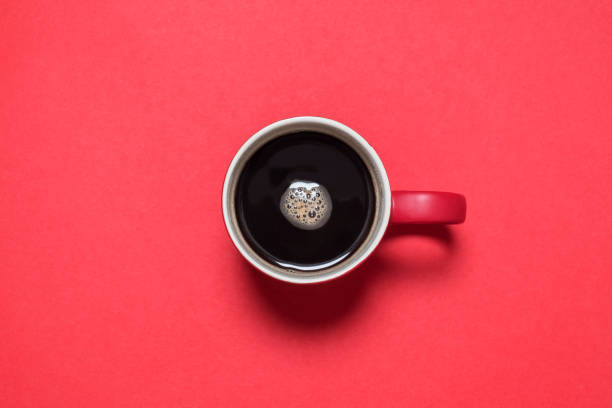 Black coffee in red cup on red background Red cup of black coffee from above on a matching red background with copy space and room for text black coffee stock pictures, royalty-free photos & images