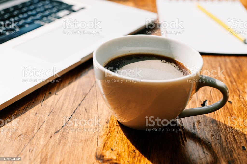 Black coffee, laptop on a desk in bright sunshine. stock photo