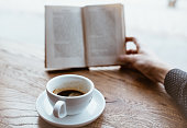 Black coffee on saucer with Human hand holding vintage book on blurred background on the wooden table next to big coffee shop window.