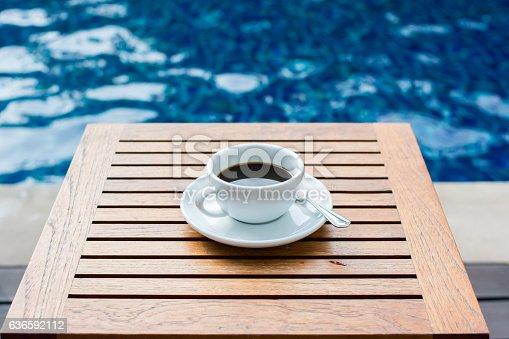 istock black coffee on table near swimming pool 636592112