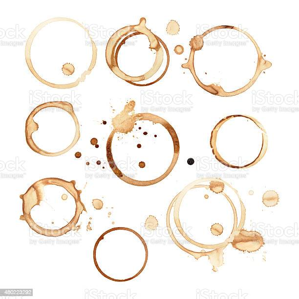 Different sized and shaped black coffee rings are isolated on a white background with a clipping path. There are splashes and drops of coffee stains around round rings where the cups sat on the paper. The stains have soaked and smeared in different shapes and sizes.
