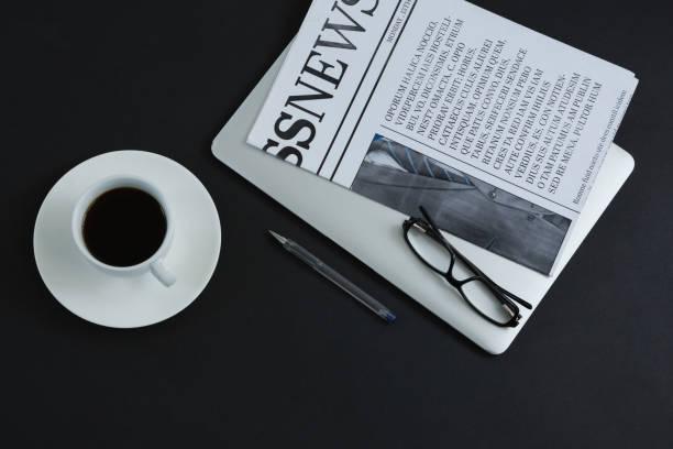 schwarzer kaffee, brille, stift, laptop und zeitung auf schwarzem hintergrund - schwarzer kaffee net stock-fotos und bilder