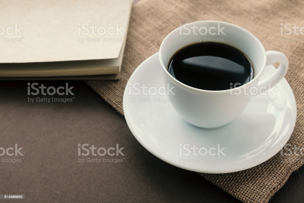 black coffee white cup and notebook on  brown paper. stock photo