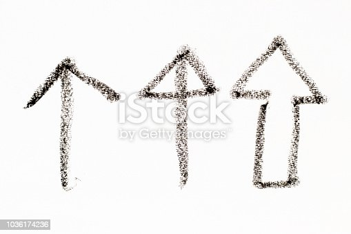 istock Black color oil pastel drawing in arrow shape on white paper background 1036174236