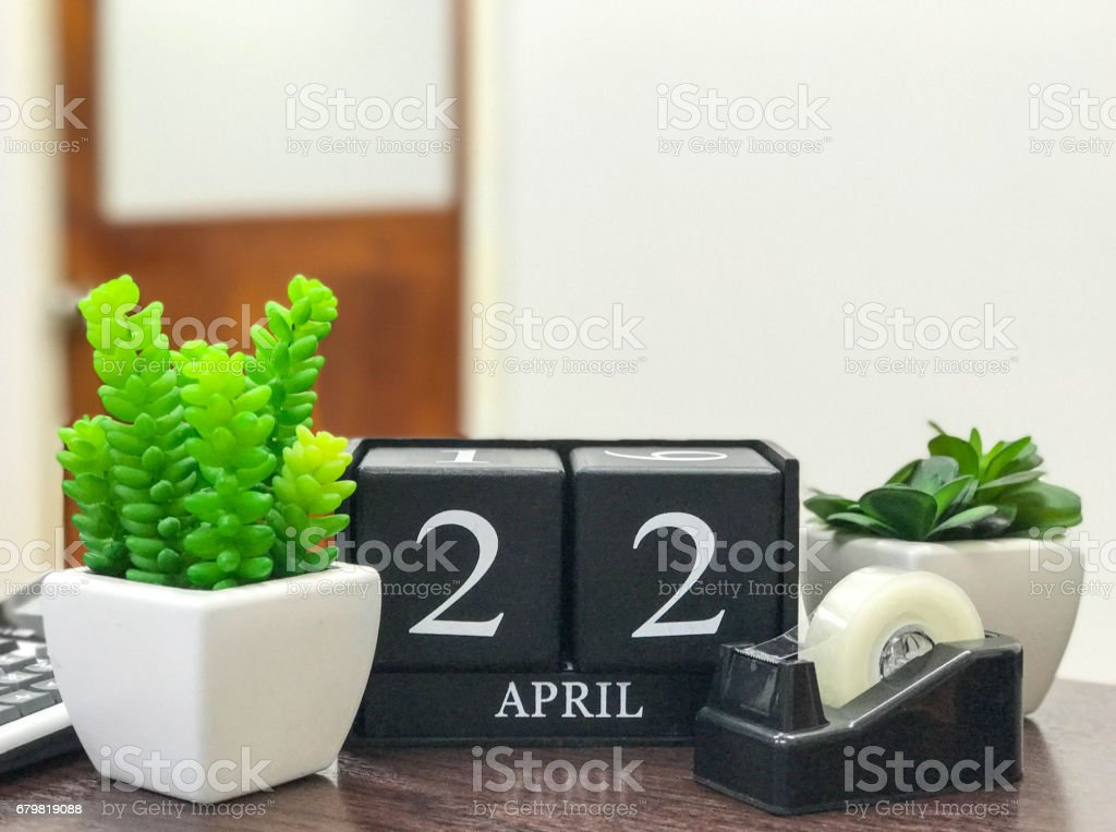 Black color wooden calendar on desk with fake small tree in pot , the date show of earthday April 22 stock photo
