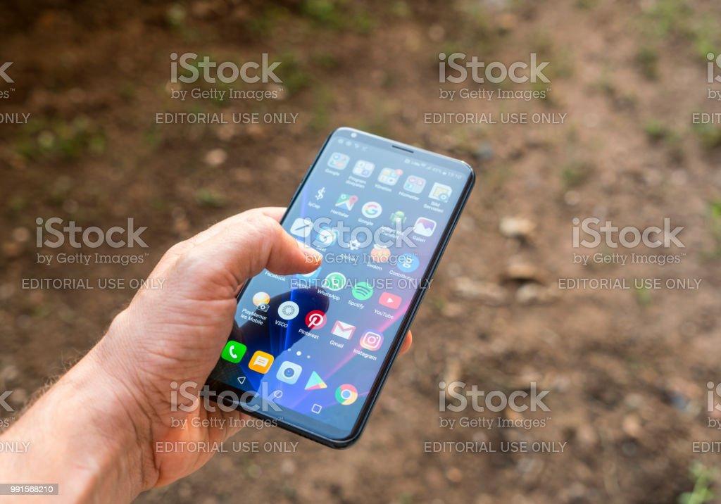Black colored LG V30 Plus smartphone in hand - Foto stock royalty-free di Adulto