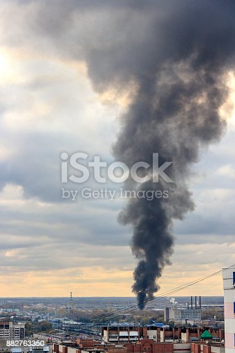 istock Black column of smoke due to the fire rises to the sky. 882763350
