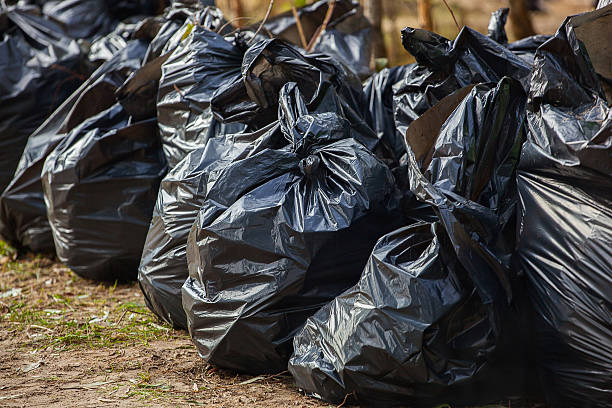 Black, complete, tied garbage bags standing together on street. stock photo