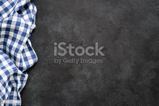 istock Black concrete background with blue checkered textile 995925668