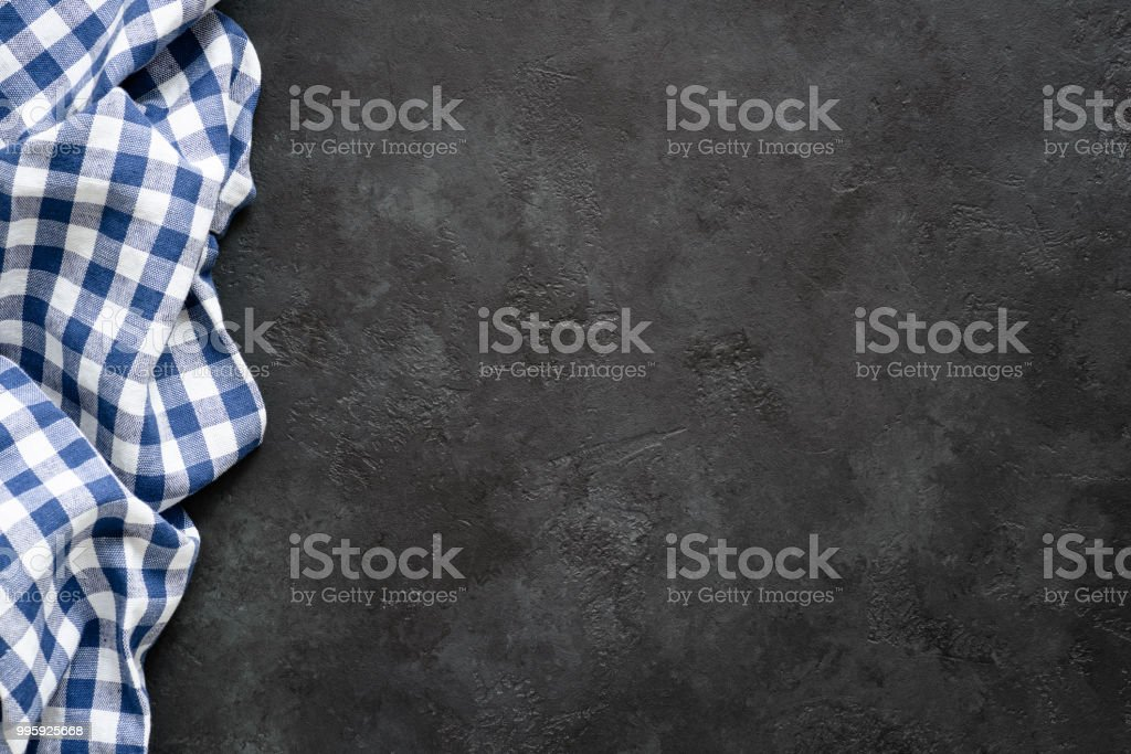 Black concrete background with blue checkered textile stock photo