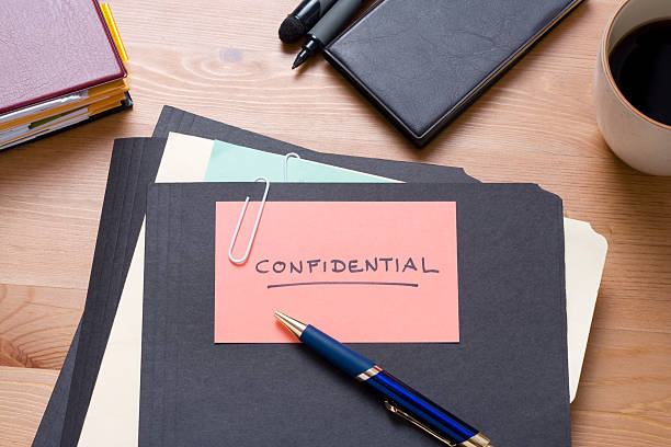 Black confidential files on a wooden desk with stationery stock photo