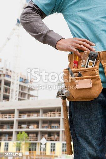 istock Black construction worker wearing tool belt 1035218748