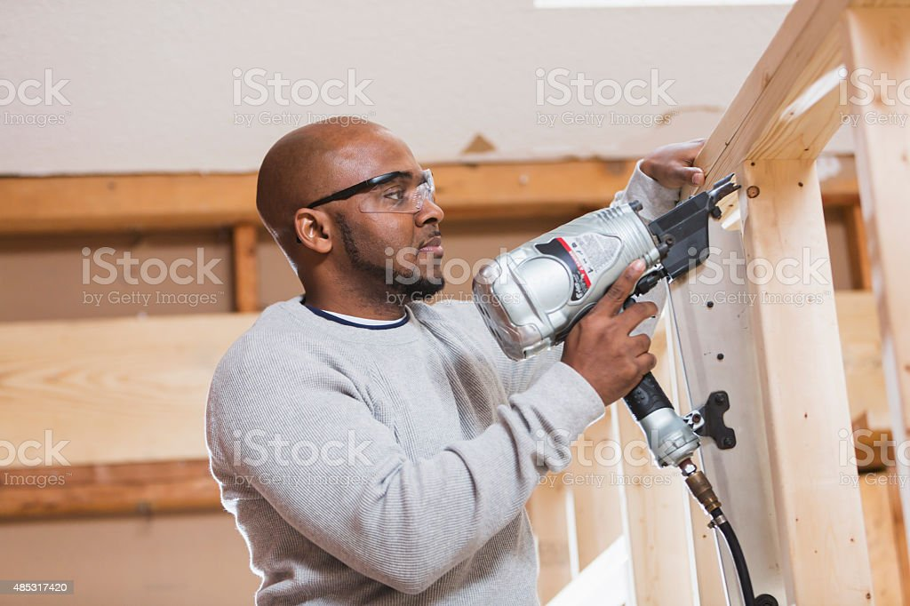 Black construction worker with nail gun stock photo