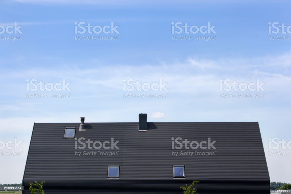 Zwart gegolfd metalen dak met dakramen foto