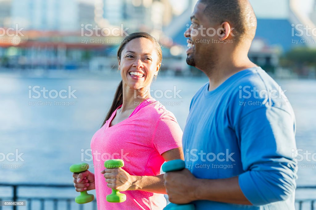 Black couple exercising together with handweights stock photo
