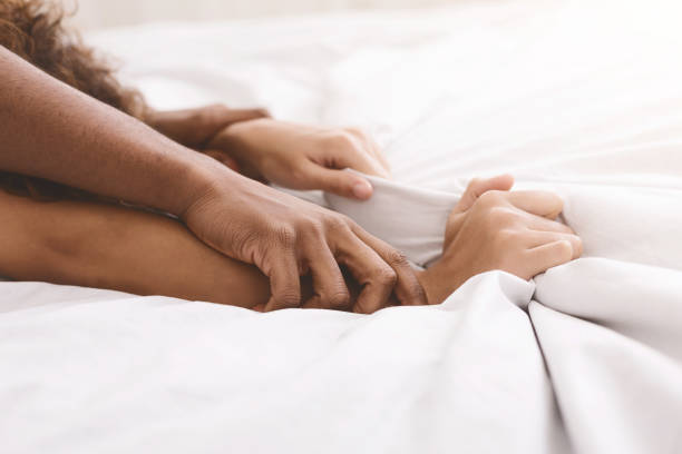 Black couple hands pulling white sheets in ecstasy stock photo