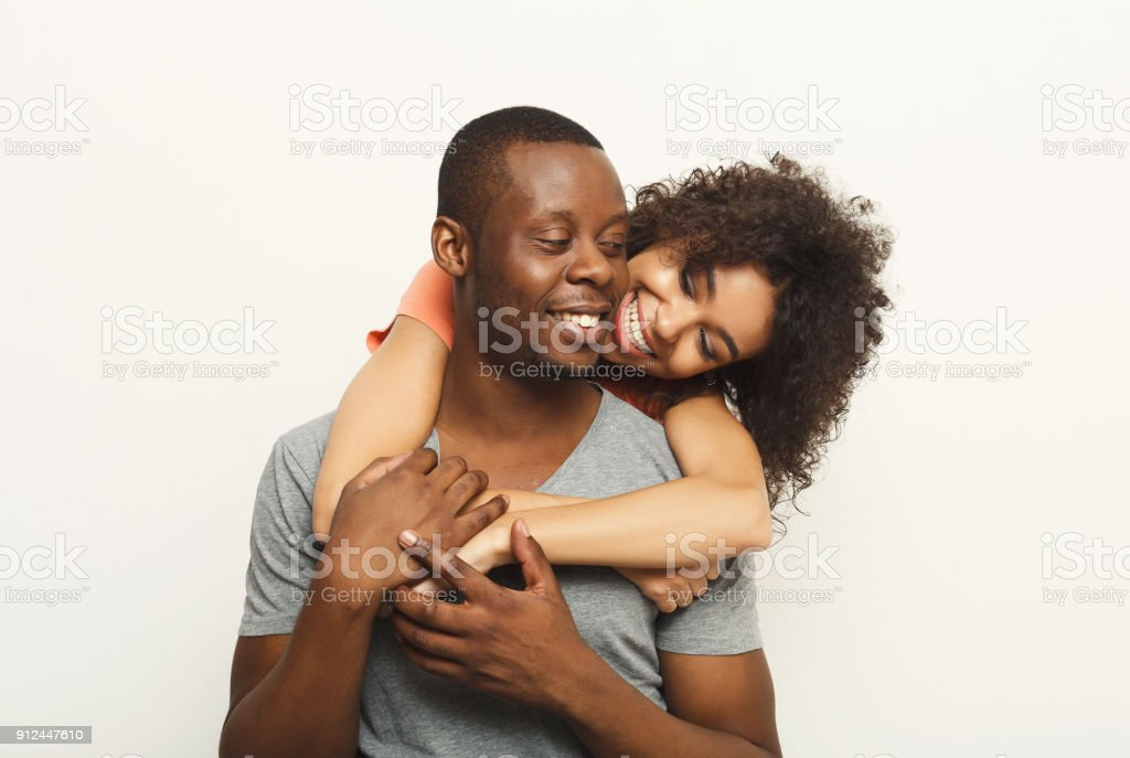 Black couple hugging and posing at white background stock photo
