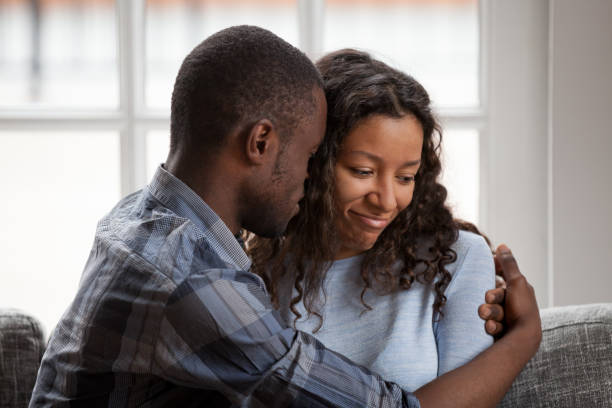 Black couple in love after quarrelling at home stock photo