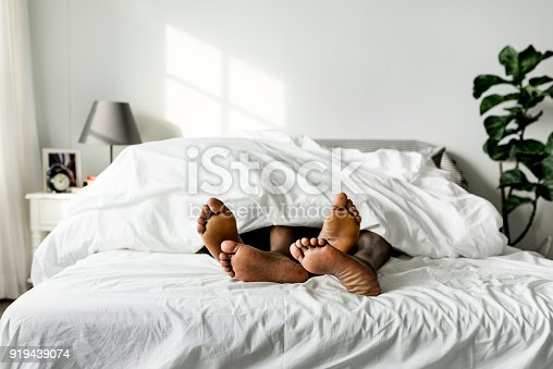 istock Black couple lying on bed together sex concept 919439074