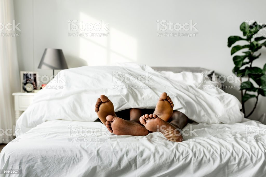 Black couple lying on bed together sex concept stock photo