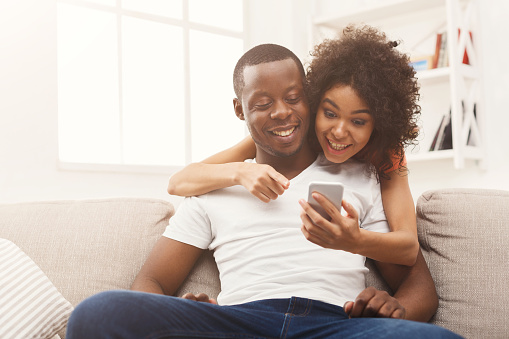 istock Black couple making using smartphone at home 936148138