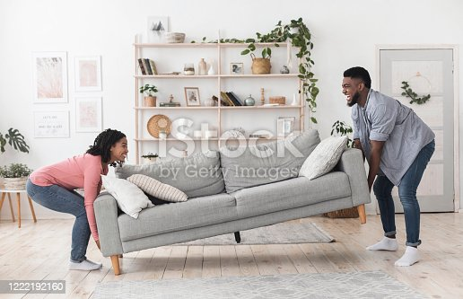 Happy african american couple moving sofa in living room, replacing furniture at home, side view
