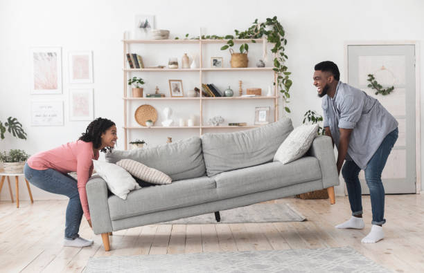 Black couple moving sofa in living room, replacing furniture at home stock photo