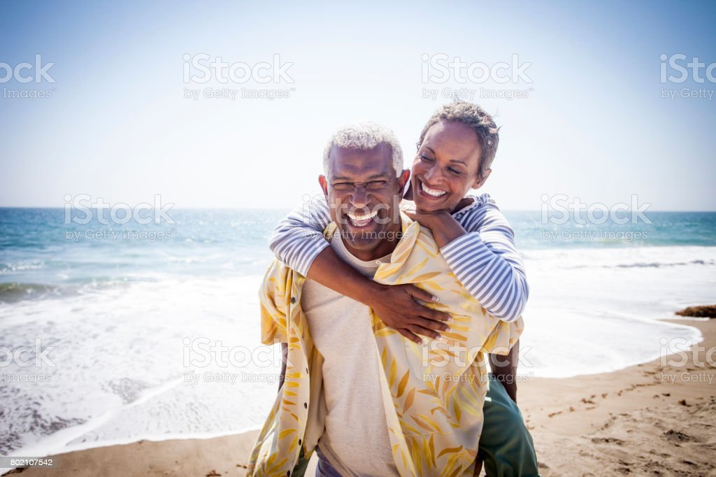 Black Couple Piggyback on Beach stock photo