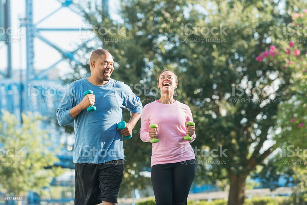 Black couple running together in park, laughing stock photo