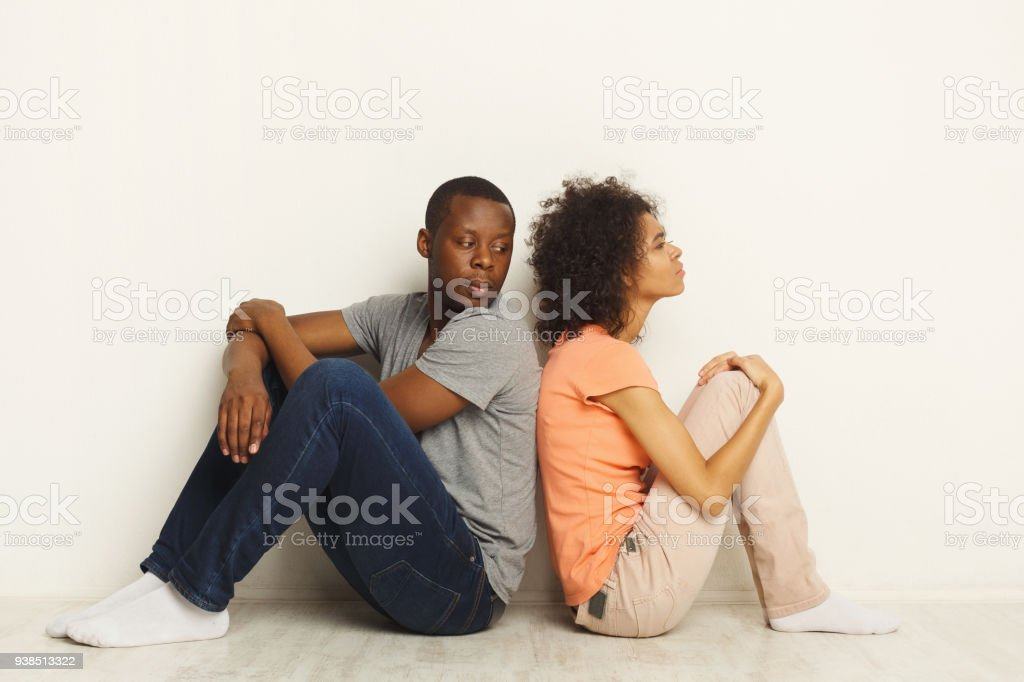 Black couple sitting on floor at new apartment stock photo