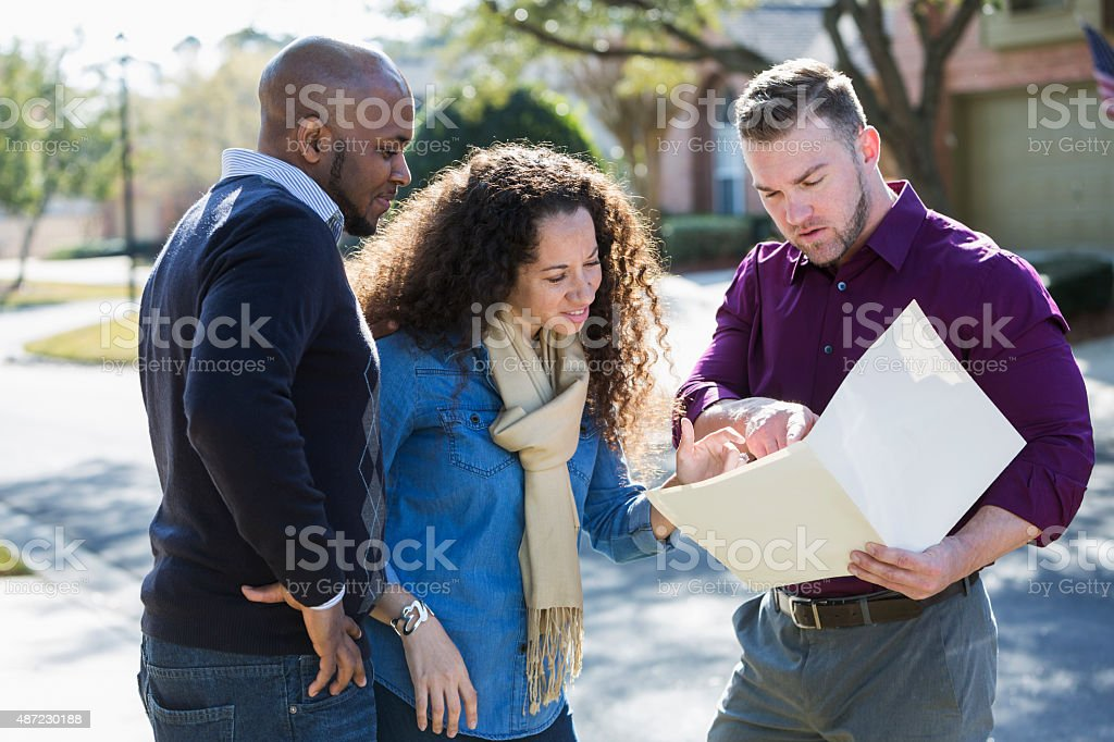 Black couple standing on residential street with agent stock photo