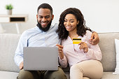 istock Black couple using laptop and debit credit card at home 1299553854