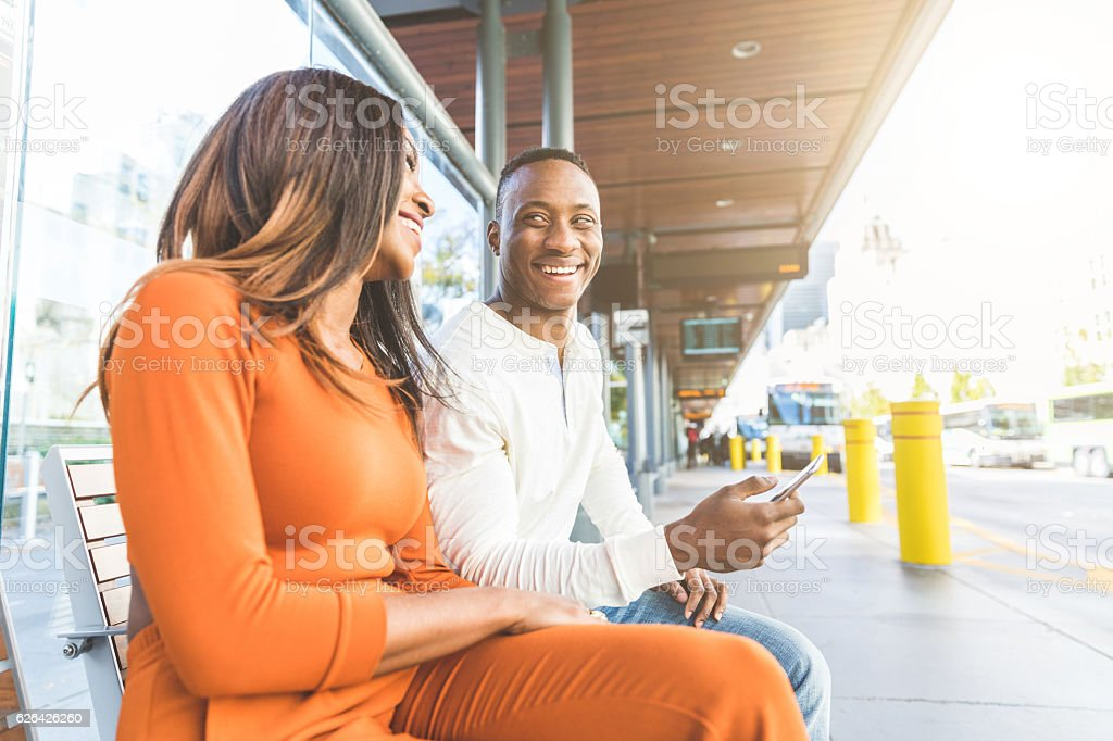 Black couple waiting for the bus at station stock photo