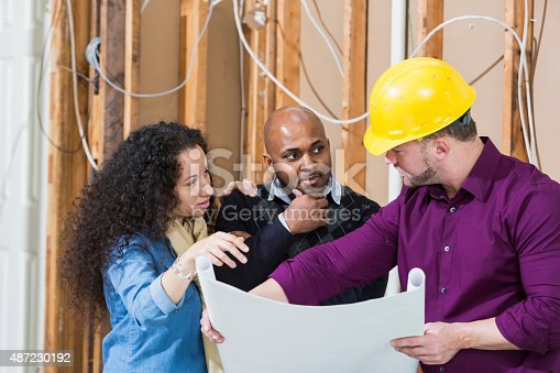 istock Black couple with contractor looking at floor plans 487230192