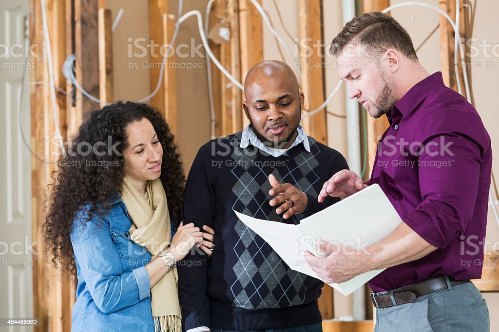 Black couple with contractor remodeling home stock photo