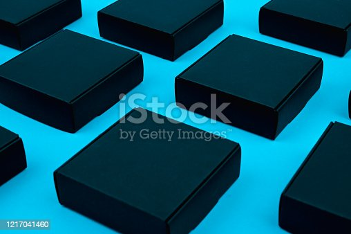 871774704 istock photo black cubes flow. black boxes on blue. black boxes on a blue background on a flat lay. Black square on blue 1217041460