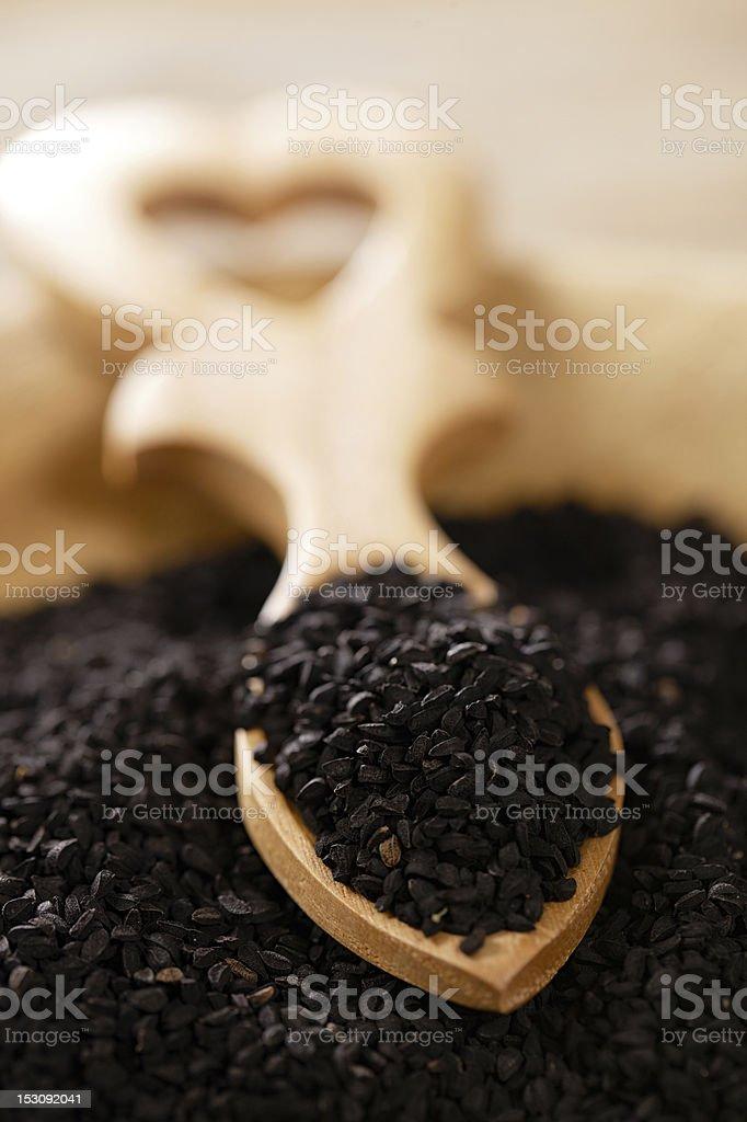 black cumin caraway  onion seeds in heart shape wooden spoon stock photo